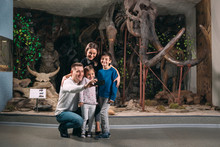 A Family Takes A Selfie Against A Mammoth Skeleton At The Museum Of Paleontology.