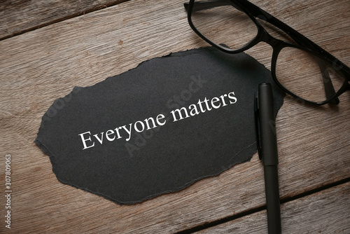 Fototapety, obrazy: Glasses,pen and piece of black paper written with Everyone Matters on wooden background.