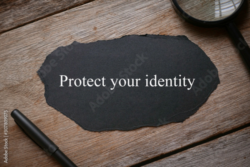 Fototapety, obrazy: Top view of magnifying glass,pen and piece of black paper written with Protect Your Identity on wooden background.