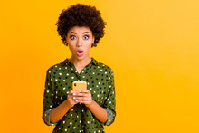Photo Of Beautiful Shocked Dark Skin Wavy Lady Open Mouth Hold Telephone Read Advert Unbelievable Big Shopping Prices Wear Green Dotted Shirt Isolated Yellow Color Background