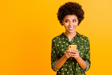Photo Of Beautiful Dark Skin Wavy Lady Hold Telephone Hands Read Good Youth News Look Empty Space Advert Wear Green Dotted Shirt Isolated Yellow Color Background