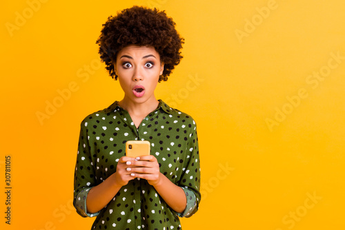 Photo of beautiful shocked dark skin wavy lady open mouth hold telephone read advert unbelievable big shopping prices wear green dotted shirt isolated yellow color background - 307811015