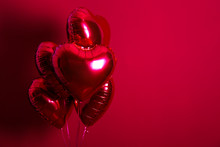 Celebrating Saint Valentine's Day With Heart Shaped Red Foil Air Balloon. Gift For Loved Woman On Special Occasion With Romantic Symbols, Women`s Day. Close Up, Copy Space, Background, Isolated.
