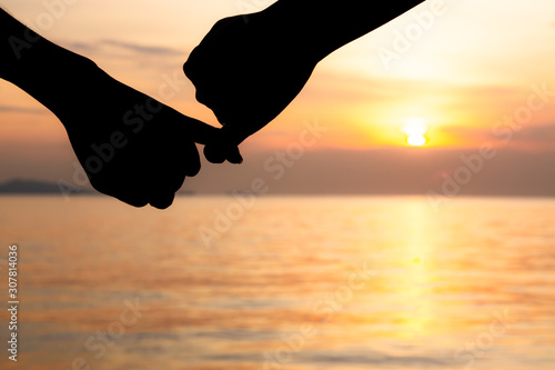 Obraz na plátne Silhouette of hand to pinky promise, pinky swear in front of the sun during sunset time