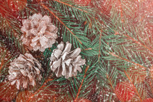 Top View Of Three Cones Covered With Hoarfrost On Frozen Fluffy Green Spruce Branches With Swirling Snowflakes, Blurred Red Lights Of Garland And Copy Space. Christmas, New Year Greeting Card Concept.