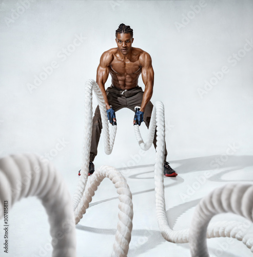 Muscular man working out with heavy ropes Canvas Print