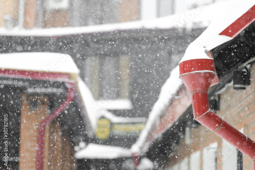 Winter background - snowy winter houses and drainpipes in defocus Canvas Print