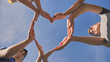 canvas print picture - A group of friends makes a heart shape out of their hands.