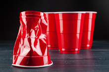 Wooden Table With Red Cups And...