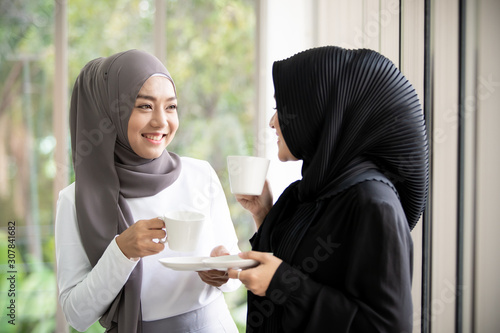 Fotografía  Two Asian Muslim woman standing and talking in the office with a cup of coffee