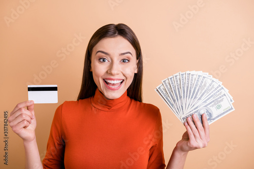 Fototapeta Photo of cheerful charming cute beautiful business woman showing you two ways of payment while smiling toothily wearing turtleneck isolated pastel beige color background obraz