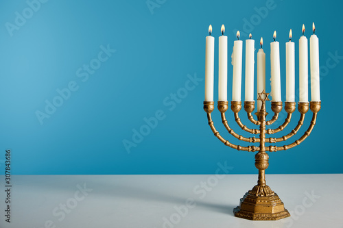 Fotografie, Obraz burning candles in menorah isolated on blue