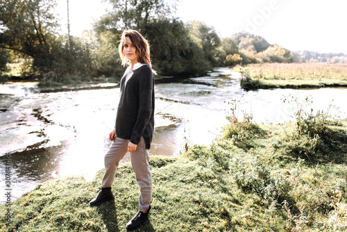 Gentle portrait of beautiful girl or woman in sweater in backlight on river back Canvas Print