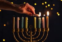 Cropped View Of Man Lighting Up Candles In Menorah On Black Background With Bokeh Lights On Hanukkah