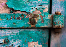 Metal Hinge And Rusty Screws On A Weathered Door With Fading Paint
