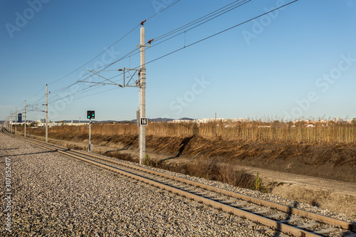 Tall weed grass behind a receding train track with overhead wires in a generic s Canvas-taulu