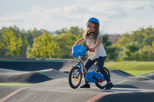 The Bike Lane For Children. Children Have Fun On The Race Pump Track. A Child In A Blue Helmet Riding A Bicycle For Safety