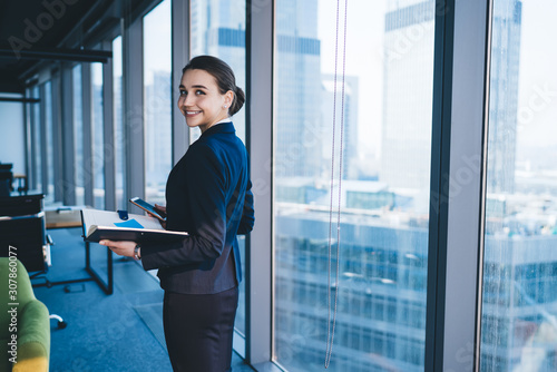 Fototapety, obrazy: Cheerful businesswoman with smartphone looking at camera in office