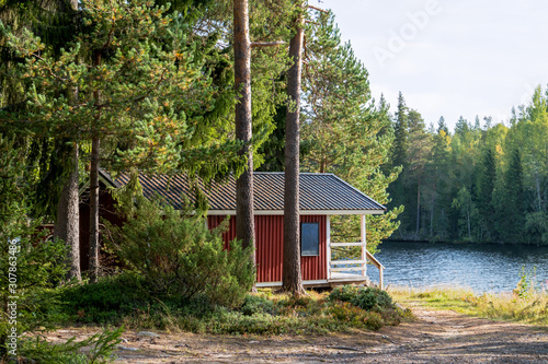 Fotografía Red wooden finnish traditional cabins cottages in green pine forest near river