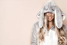 Beautiful Blond Woman Wearing A Winter Pajama, A Bunny Costume, Smiling Happily. Fashion Model In Easter Bunny Costume. Christmas And Easter Concept.