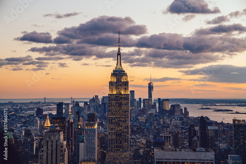 Fototapeta Aerial view of skyscrapers and towers in midtown skyline of Manhattan with evening sunset sky. Scenery cityscape of financial district with famous New York Landmark, illuminated Empire State Building obraz na płótnie