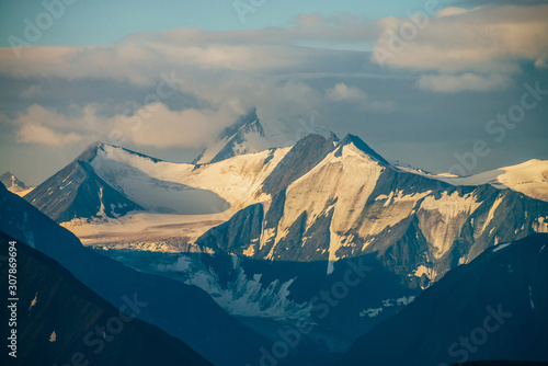 Fototapeta  Atmospheric alpine landscape with big snowy mountains among low clouds in golden hour