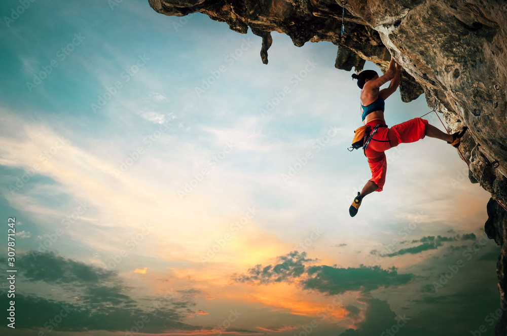 Fototapeta Athletic Woman climbing on overhanging cliff rock with sunset sky background.
