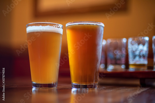 two pints of craft beer on bar counter at night Wallpaper Mural