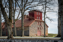 View Of Old Drying Barn Through The Trees In A Countryside During The Spring Months. Olustvere Manor Complex. Estonia.