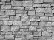 Modern retro style round rock stone uneven wall background on a wall of the building in the outdoors with rough texture and pattern in black and white