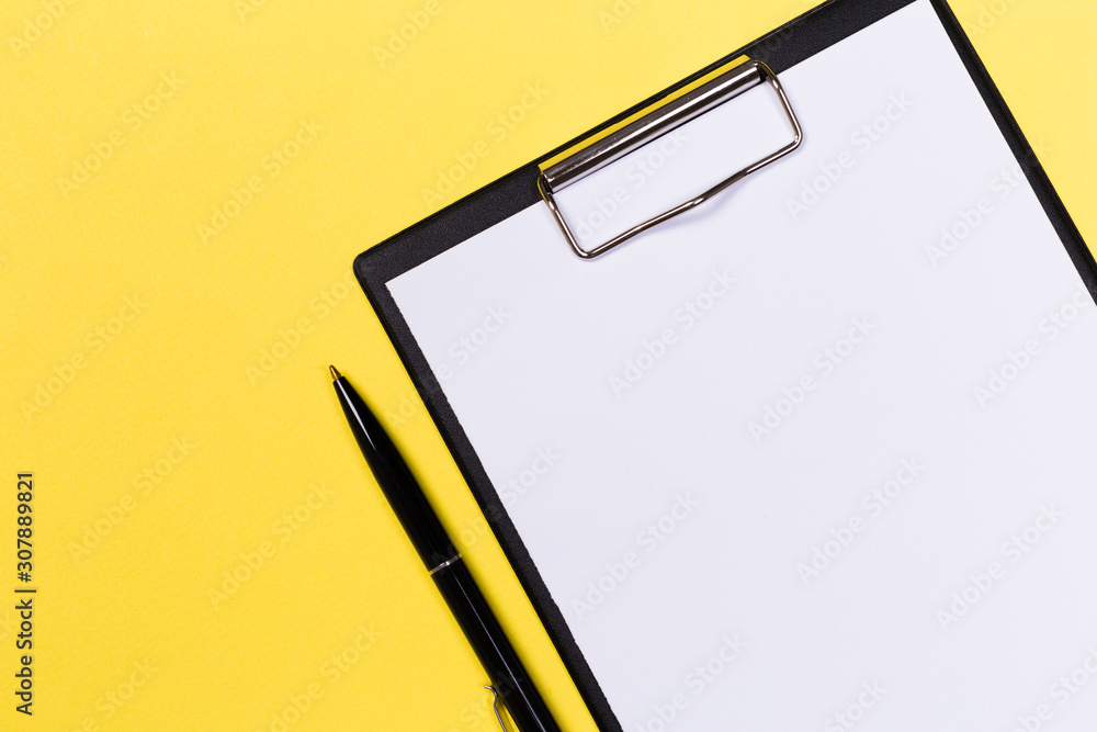 Fototapeta Clipboard with white sheet and pen on a yellow background. View from above. space for text