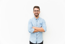 Joyful Positive Guy Posing With Arms Folded. Handsome Young Man In Casual Shirt And Glasses Standing Isolated Over White Background. Happy Man Portrait Concept