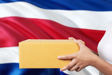 Costa Rica Delivery Service. International Shipment Theme. Woman Courier Hand Holding Brown Box Isolated On National Flag Background.