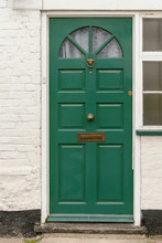 Green Front Door With A Knob, A Knocker And A Mail Slot