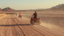 Quad Bike Ride Through The Desert Near Sharm El Sheikh, Egypt.Adventures Of Desert Off-road On ATV.Sand And Sand Borkhan. Rock And Sunset. Quad Cycle Travel. Excursion With People.
