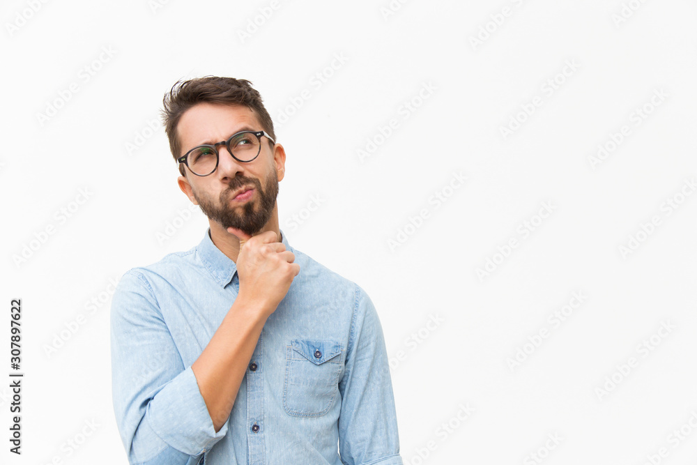 Fototapeta Thoughtful male customer thinking hard, looking away at copy space, leaning chin on hand. Handsome young man in casual shirt and glasses standing isolated over white background. Special offer concept