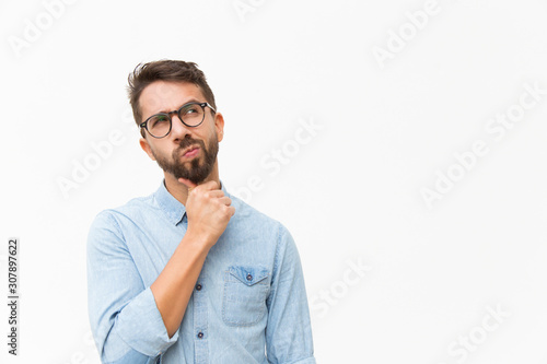Obraz Thoughtful male customer thinking hard, looking away at copy space, leaning chin on hand. Handsome young man in casual shirt and glasses standing isolated over white background. Special offer concept - fototapety do salonu