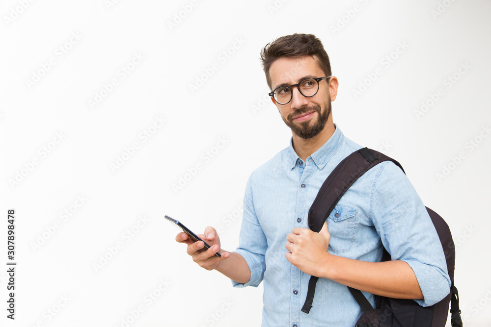 Fototapeta Positive male tourist with backpack using mobile phone, looking away. Handsome young man in casual shirt and glasses standing isolated over white background. Communication or travel concept