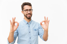 Happy Joyful Guy Showing OK Gesture With Both Hands. Handsome Young Man In Casual Shirt And Glasses Standing Isolated Over White Background. Customer Satisfaction Concept
