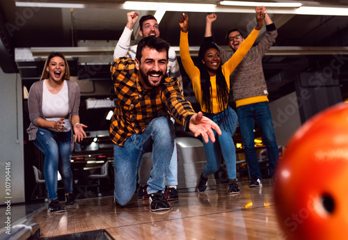Group of friends enjoying time together laughing and cheering while bowling at club. - 307904416