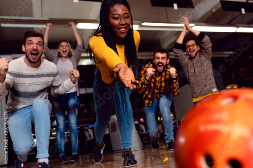 Group of friends enjoying time together laughing and cheering while bowling at club Fototapete