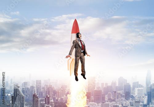 Businessman in aviator hat flying on rocket Canvas Print