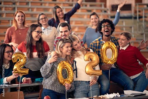 Photo sur Aluminium Individuel happy students celebrating 2020 new year toghether in university
