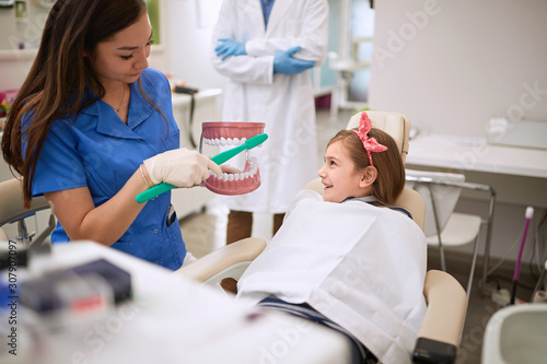 Photo Dental assistant showing to child how to brushing her teeth
