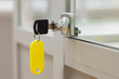 Lock with key with yellow tag on gray office glass furniture. Side view.