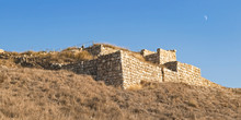 The Stone City Gates And Retaining Wall Of Biblical Era Tel Lachish In Israel With The Moon Setting In A Clear Blue Sky In The Background