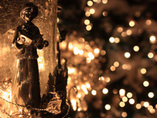 Christmas Caroler Ornament With White Lights In Background