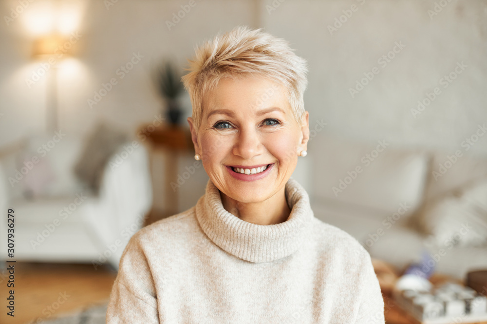 Fototapeta Close up image of happy good looking elegant fifty year old woman wearing warm cozy jumper, pearl earrings and short stylish hairdo being in good mood sitting in living room, smiling broadly at camera