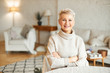 Leinwanddruck Bild - People, coziness, domesticity and season concept. Charming beautiful retired woman spending leisure time indoors at home looking at camera with confident smile, keeping arms folded on her chest