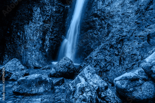 Little waterfall among stones in blue color